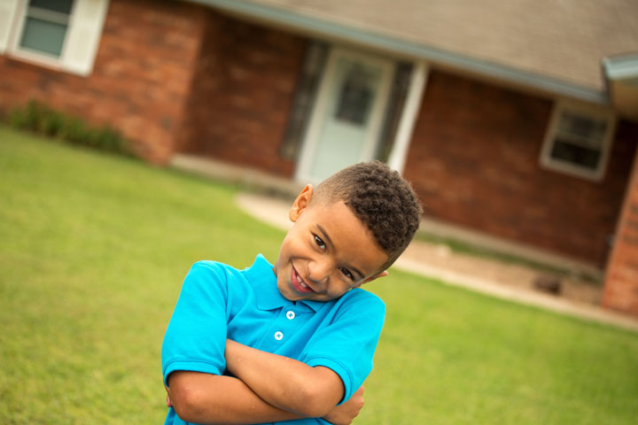Boy crossing his arms and smiling in the middle of the front yard.