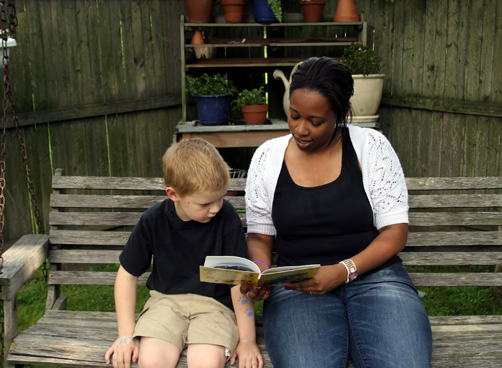 Woman reading a book to a young boy on a wooden outdoor bench.
