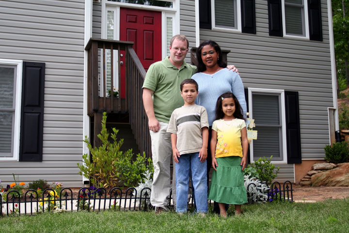 Photo of multiracial family standing outside their home.