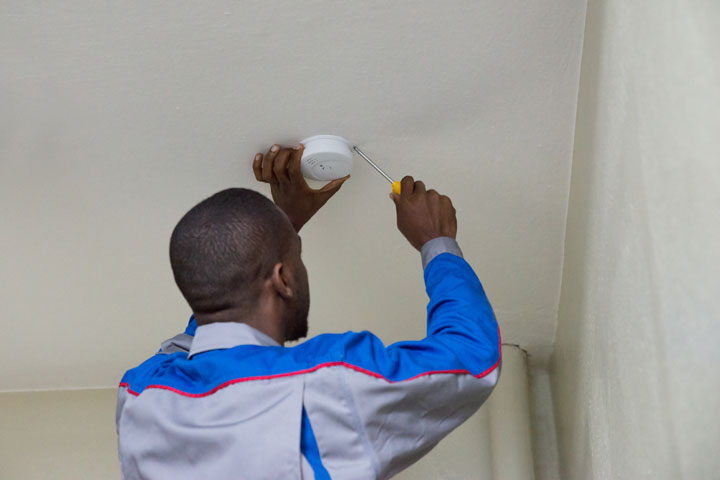 Man installing a new smoke alarm on the ceiling with a screwdriver.
