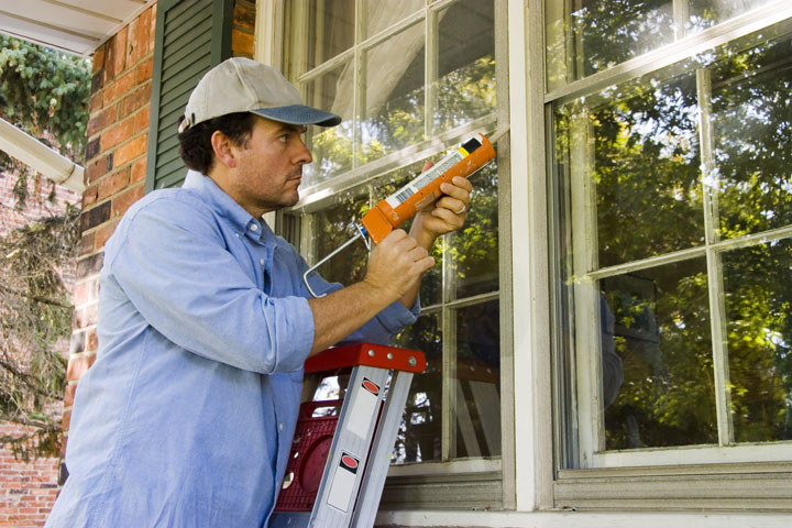 White man in a blue work shirt leaning against a ladder and using caulk to seal in a window.