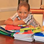 Boy leaning over a stack of school supplies with a grin on his face.