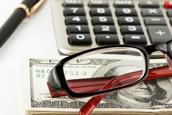 Glasses sitting on top of a stack of one hundred dollar bills, with calculator in background.