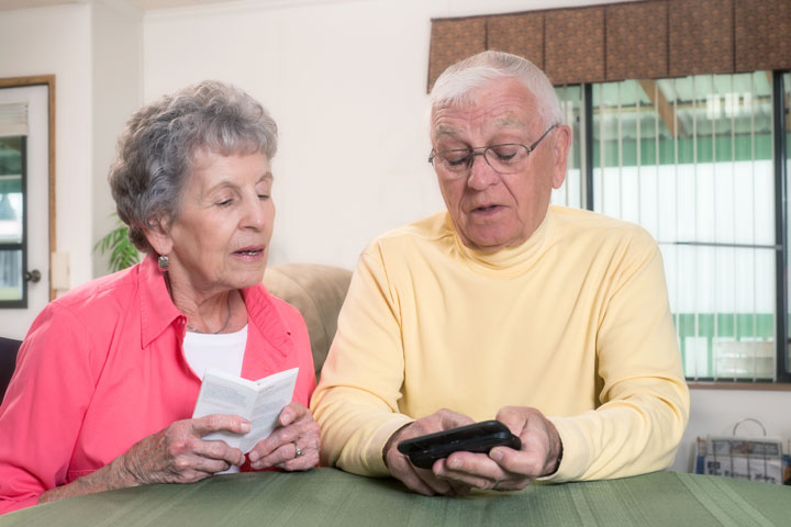 White, elderly couple holding and looking at a text-slider cell phone.