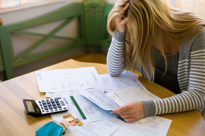 Blonde woman with her head in her hands while looking at bills on the kitchen table.