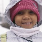 Young smiling girl in a winter coat with hat and scarf. Winter coats program.
