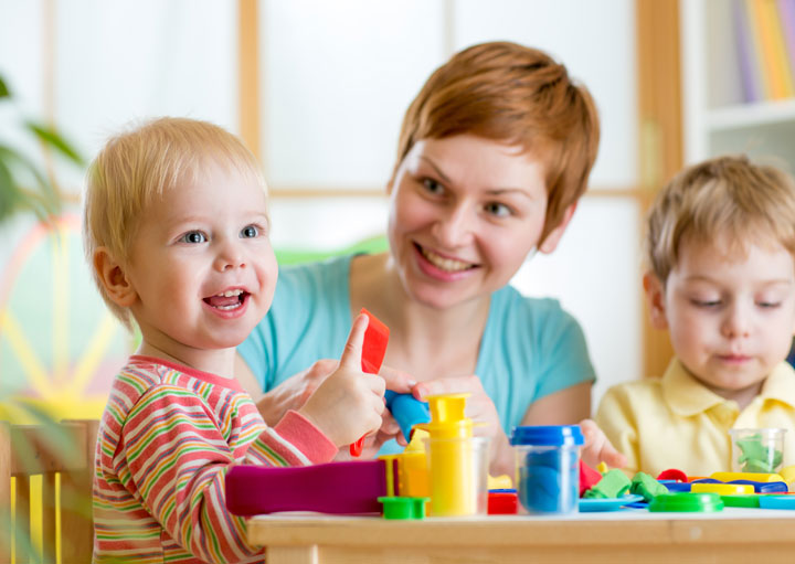 Blonde toddler boy smiling with red-haired childcare worker woman in the background.