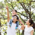 Asian family in the park, with father pointing to the sky and son on his shoulders and mom next to them.