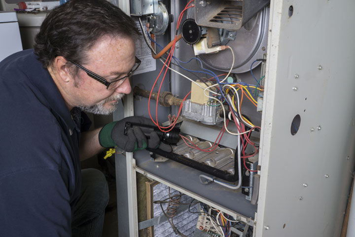 Electrician inspecting a furnace.