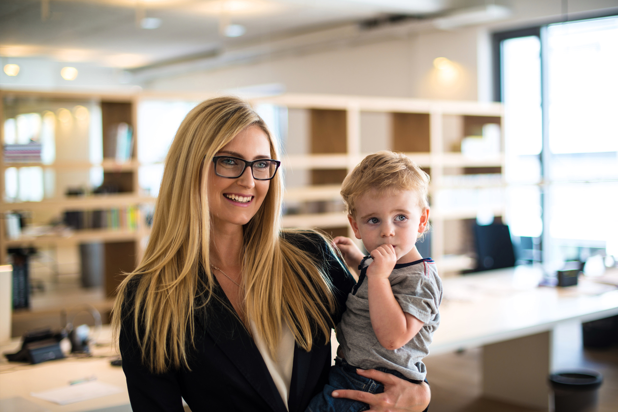 Young woman in business attire, holding small child.