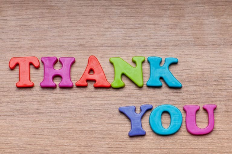 Thank You spelled out with child's magnetic letters on wood grain background.