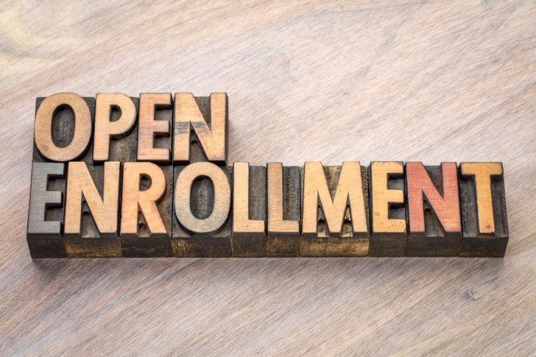 "Raised type letters on a woodgrain background that say ""Open Enrollment"""