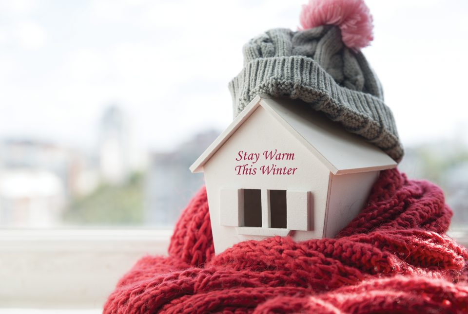 Small craft house with a scarf and hat to signify staying warm in the winter