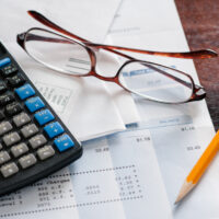 Bills with calculator and glasses on a table
